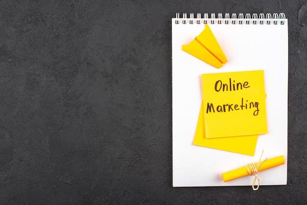 暗い背景のメモ帳に黄色の付箋に書かれたトップビューのオンラインマーケティング