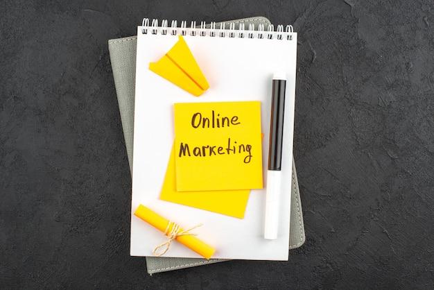 Marketing online vista dall'alto scritto su una nota adesiva pennarello nero su blocco note su sfondo scuro