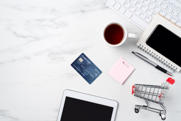 Top view of online shopping concept with credit card and electronics isolated on office marble white table background.