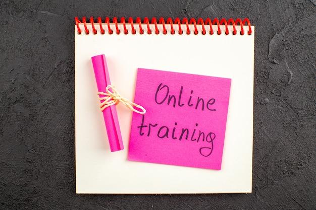 黒のメモ帳にピンクの付箋に書かれたトップビューオンライントレーニング