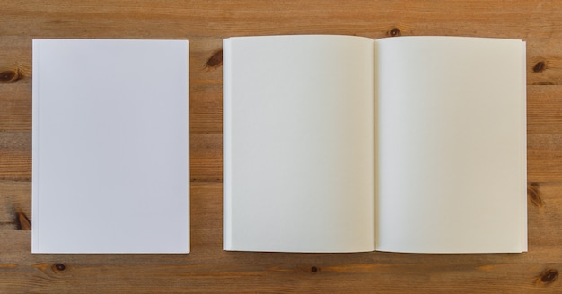 Top view of open blank book next to pieces of paper