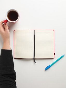 Top view of an open blank red notebook in the center, a blue pen beside it and a female hand