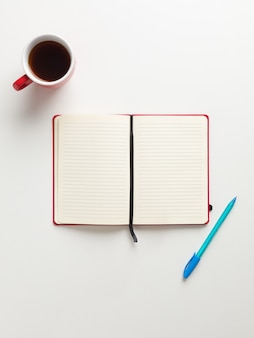 Top view of an open blank red notebook in the center, a red cup of coffee and a blue pen