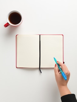 Top view of an open blank red notebook in the center, a red cup of coffee, and a female hand