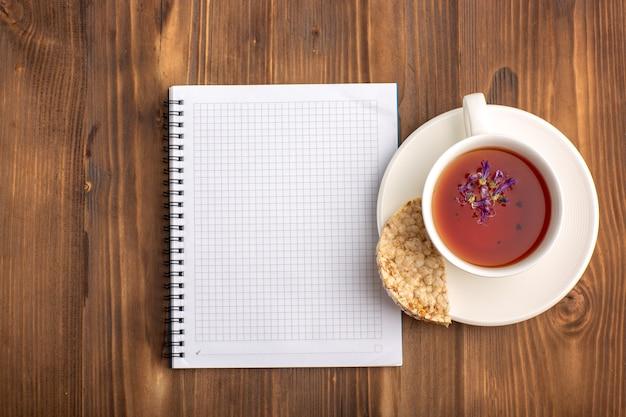 茶色の机の上にお茶を入れた上面図の開いた青いコピーブック
