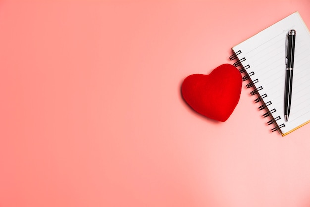 Top view of open book red heart. book open with pen on pink background.