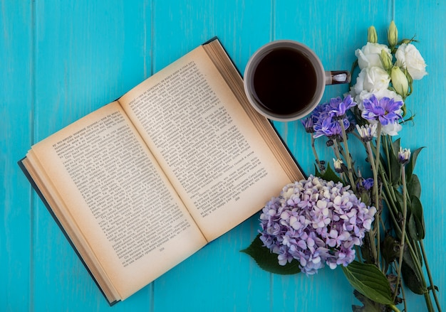 Top view of open book with cup of coffee and flowers on blue background