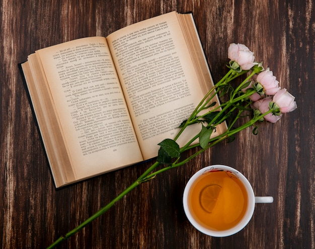 Top view of open book with pink roses and a cup of tea on wooden surface