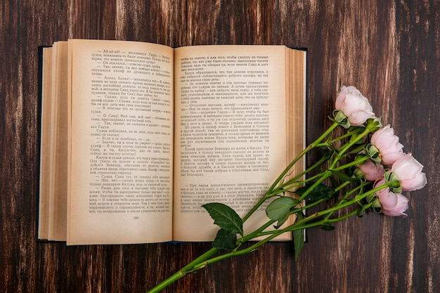 Top view of open book with pink roses on a wooden surface