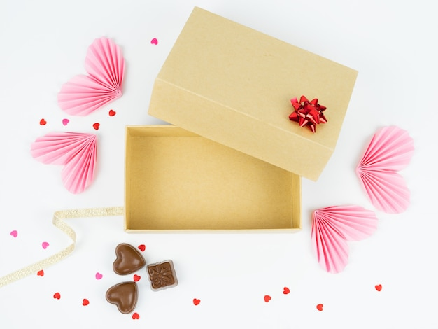 Top view of open cardboard box with valentine's day, anniversary, mother's day and birthday decoration. free space to put the products. valentine's day concept.