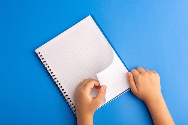 Bambino di quaderno aperto vista dall'alto che lo strappa sulla superficie blu