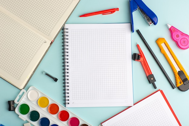 Top view open copybook with colorful paints on ice blue surface