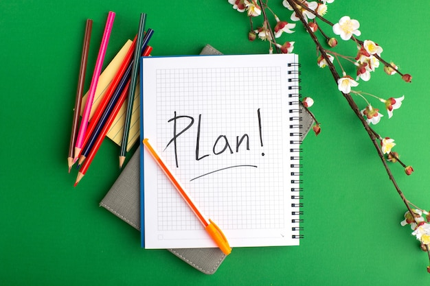 Top view open copybook with colorful pencils and flowers on green surface