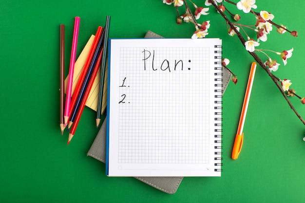 Top view open copybook with colorful pencils and flowers on the green surface