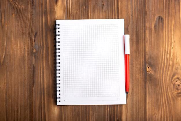 Вид сверху открытая тетрадь с ручкой на коричневом столе