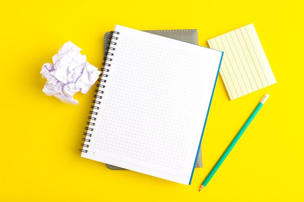 Top view open copybook with pencil on yellow surface