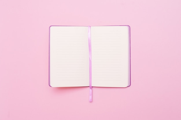 Top view of open empty notebook on pastel pink colorful background