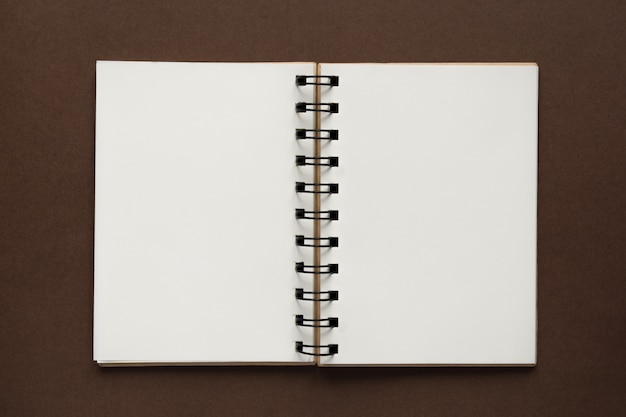 Top view of open empty notebook with cover from recycled paper on brown colorful background