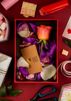 Top view of an open gift box with coral color rose flower and small paper card with purple ribbon and petals on red table with scissors, stapler, white chocolate and marshmallow