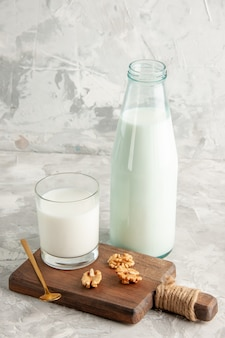 Top view of open glass bottle and cup filled with milk spoon and walnut on ice wall