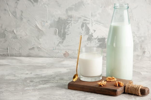 Top view of open glass bottle and cup filled with milk spoon and walnut on the left side on ice background