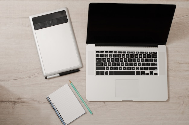 Top view of the open laptop, graphics tablet and notebook on a wooden table