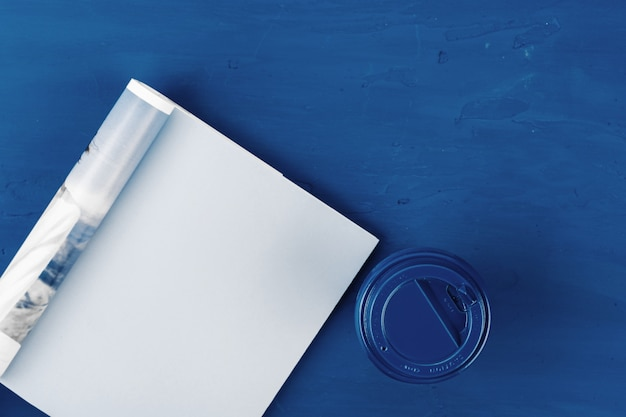 Top view of open magazine page with copy space on classic blue background