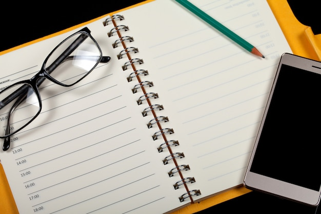 Top view of an open note book, glasses, pen and smartphone on a black background.