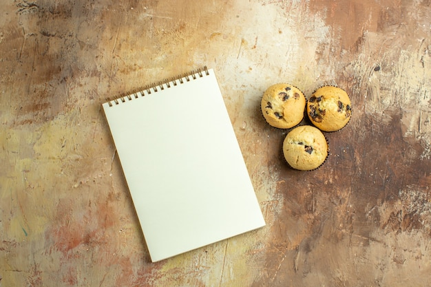 Top view of open notepad with delicious cakes on brown surface