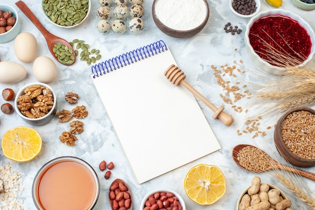上面図開いたメモ帳、卵粉ゼリー、白いナッツ生地の色のケーキ、甘いパイの写真の砂糖にさまざまなナッツと種子
