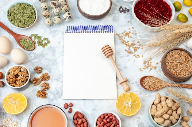 Top view open notepad with eggs flour jelly different nuts and seeds on white nut color cake sweet pie photo sugar dough
