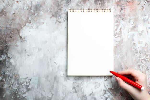 Vista dall'alto del blocco note aperto con disegno femminile su di esso su superficie bianca