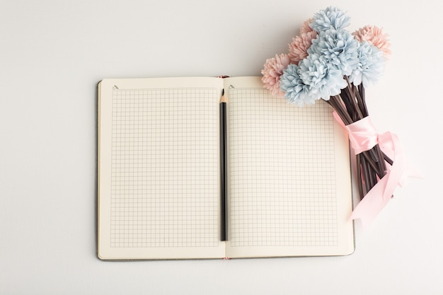 Top view open notepad with flower and pencil on white surface