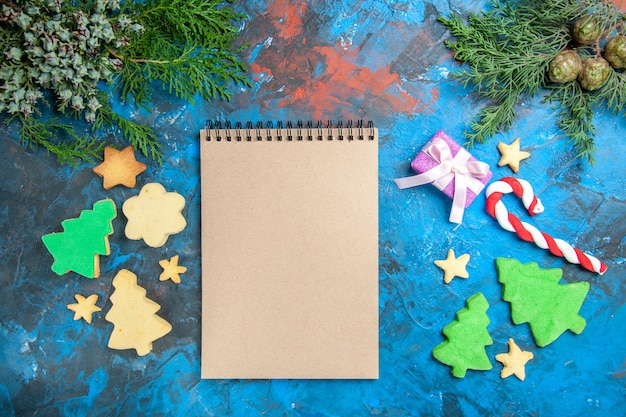 Top view of open notepad with presents on blue surface