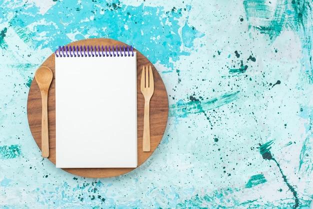 水色の背景紙写真カラーペンに木製のフォークとスプーンで上面図オープンメモ帳