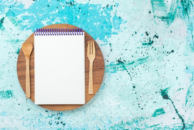 Top view open notepad with wooden fork and spoon on the light-blue background paper photo color pen