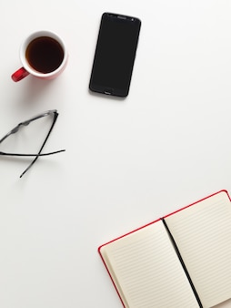 Top view of an open red notebook, a red cup of coffee, a cell phone and glasses