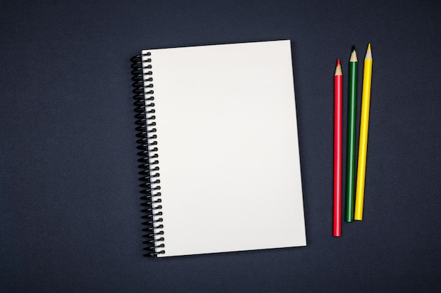 Top view of open spiral blank notebook on colorful desk