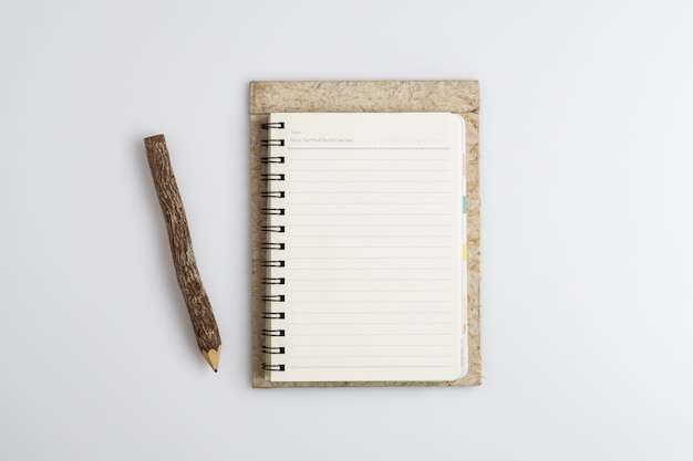 Top view of open spiral blank notebook with wooden pencil