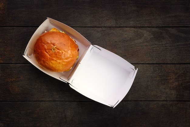 Top view of open take away box with burger on wooden table
