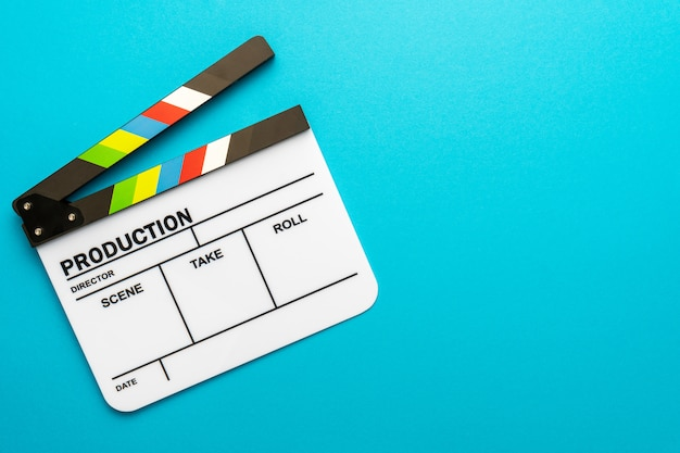 Top view of open white clapperboard on turquoise blue background