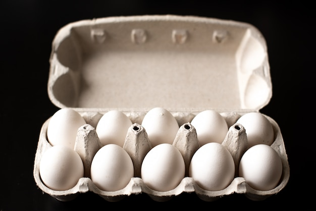 Top view of opened box with eggs on black background.