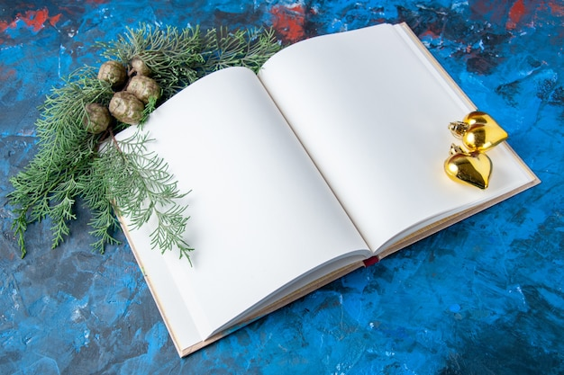 Vista dall'alto notebook aperto rami di abete coni albero di natale giocattoli su sfondo blu posto libero