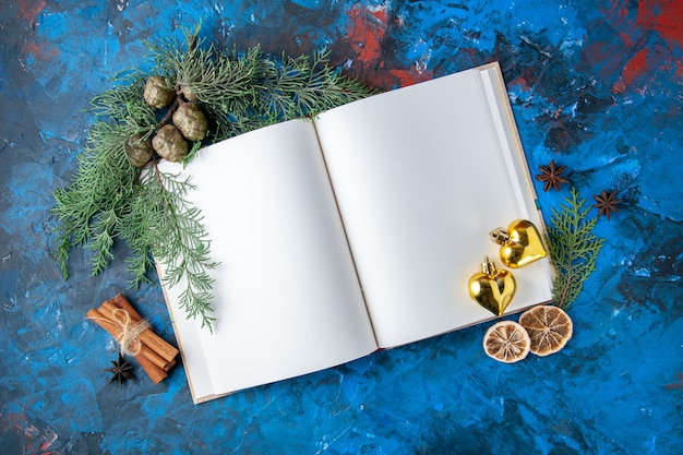 Top view opened notebook fir tree branches cones xmas tree toys on blue background free place