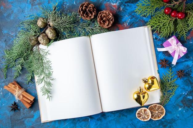 상위 뷰는 파란색 표면에 있는 노트북 전나무 나뭇가지 콘 크리스마스 트리 장난감을 열었습니다.
