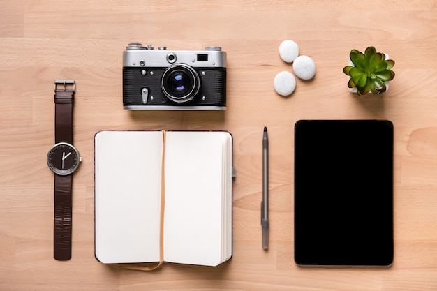 Top view of opened notepad, pen, watches, vintage camera, tablet and flower on wooden background