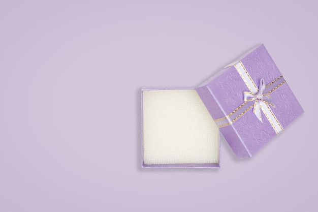 Top view of opened purple gift box on purple background
