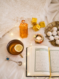 Top view opened quran with lemon tea and pastries