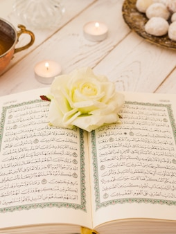 Top view opened quran with white rose