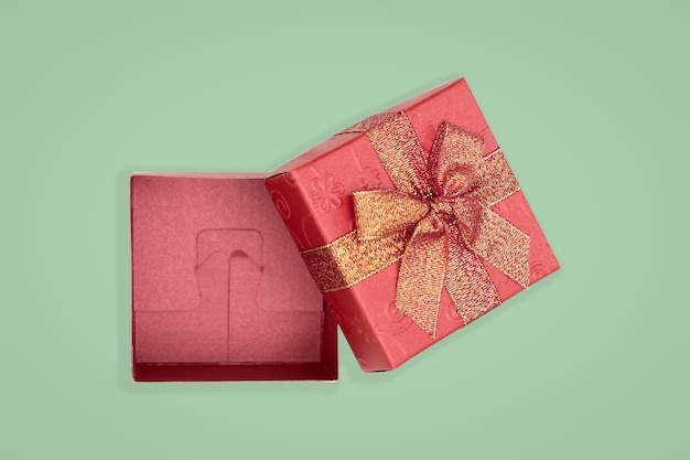 Top view of opened red gift box on green background